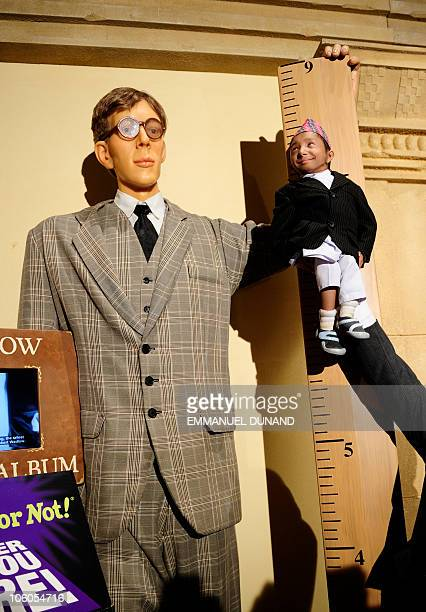 Khagendra Thapa Magar the world's smallest teen is held next to a lifesized figure of Robert Wadlow the world's tallest man ever to mark his...
