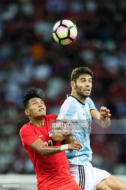 Khairul Nizam of Singapore fights for the ball with Federico Fazio of Argentina who heads the ball during the International Test match between...
