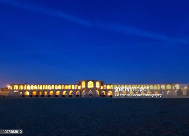 "khaju bridge (""pol-e khaju"") illuminated at late dusk over zayandeh river in isfahan, iran - ザーヤンド川 ストックフォトと画像"