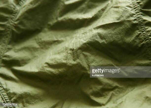 khaki green color nylon cloth wrinkles - khaki green stock pictures, royalty-free photos & images