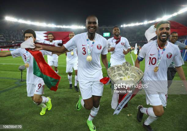Khaled Mohammed Abdelkarim Hassan and Hasan Al Haydos of Qatar celebrate with the AFC Asian Trophy following their sides victory in during the AFC...