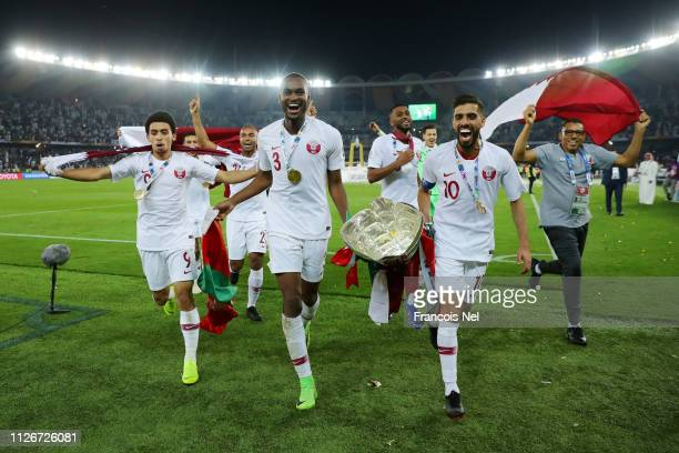 Khaled Mohammed, Abdelkarim Hassan and Hasan Al Haydos of Qatar celebrate with the AFC Asian Trophy following their sides victory in the AFC Asian...