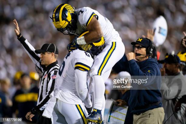 Khaleke Hudson congratulates Josh Uche of the Michigan Wolverines after a sack against Sean Clifford of the Penn State Nittany Lions as head coach...