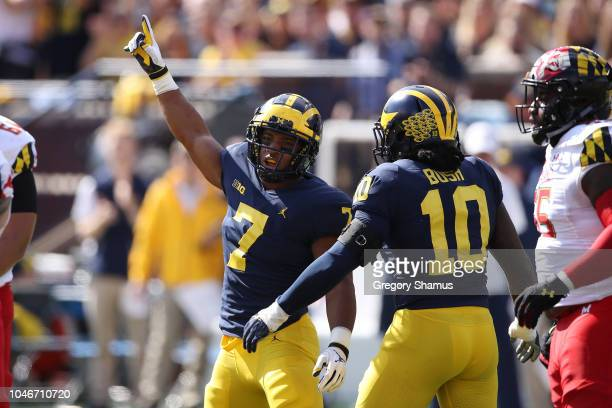 Khaleke Hudson of the Michigan Wolverines celebrates a first half tackle with Devin Bush while playing the Maryland Terrapins on October 6 2018 at...