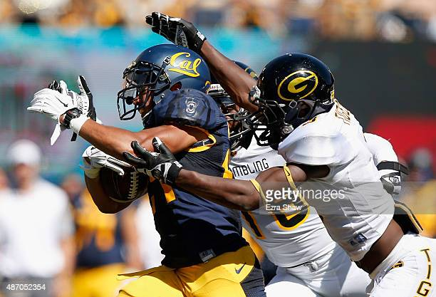 Khalfani Muhammad of the California Golden Bears is tackled by Cameron Walker and Jordan Stargell of the Grambling State Tigers at California...