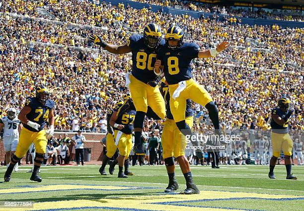Khalid Hill of the Michigan Wolverines celebrates his third quarter touchdown with John O'Korn while playing the Hawaii Warriors on September 3 2016...