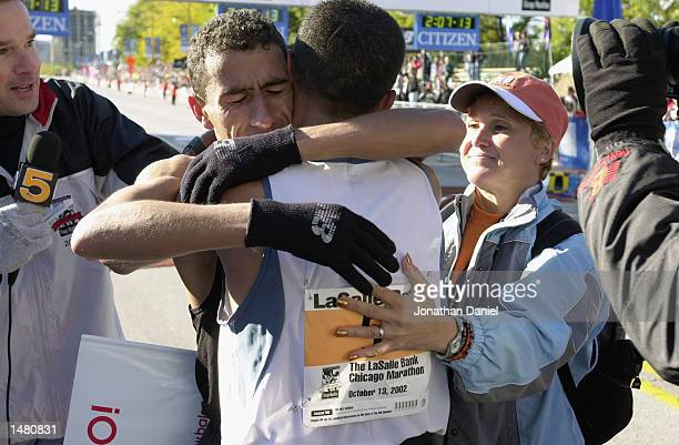 Khalid Khannouchi of New York men's winner of the Chicago Marathon hugs fellow participant fifth place finisher Abdelkhader El Mou at the finish line...