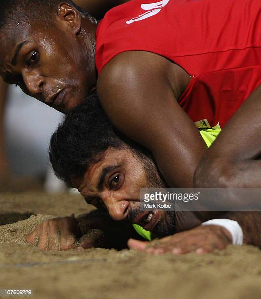 Khalid Muhammad of Pakistan reaches for the line under the tackle of Ismail AlHadi of Oman as he competes in the mens semi final match between...