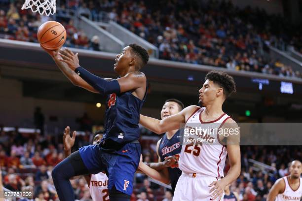 Khalil Ahmad of the CalState Fullerton Titans handles the ball against Bennie Boatwright of the USC Trojans during a college basketball game at Galen...