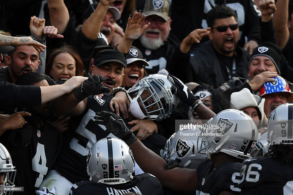 Khalil Mack #52 of the Oakland Raiders celebrates in the stands after scoring on an interception of Cam Newton #1 of the Carolina Panthers in the second quarter of their NFL game on November 27, 2016 in Oakland, California.