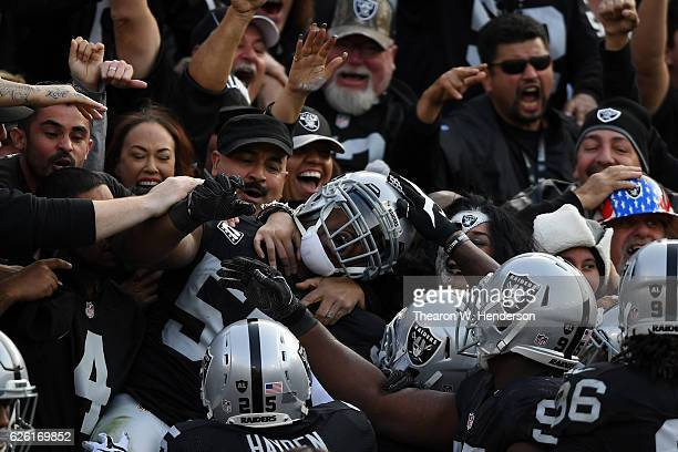 Khalil Mack of the Oakland Raiders celebrates in the stands after scoring on an interception of Cam Newton of the Carolina Panthers in the second...