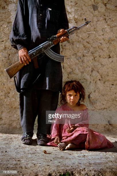 Khalil Rahman poses next to his daughter Nasrine on the Pakistani border next to the Angour Ada passage on July 2004 in Petawgai Afghanistan