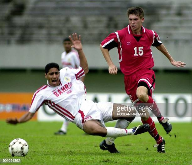 Khamis Eid Rafia of Bahrain is toppled by Kyrgyzstan's Kudrenko Igor during the World Cup Preliminary competition in Singapore 06 February 2001...