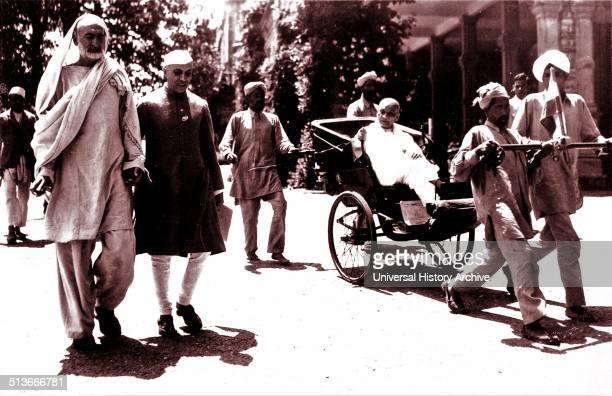 Khan Abdul Ghaffar Khan and Jawaharlal Nehru walk to a Congress meeting while Sardar Patel is pulled alongside in a rickshaw
