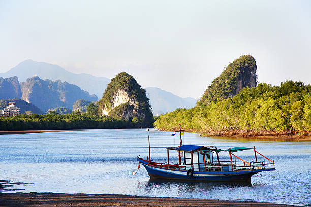Khao Knanaab Nam limestone cliffs and fishing boat at Krabi River.