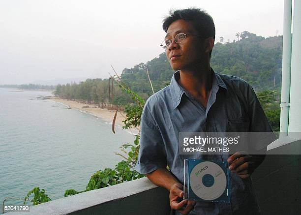 Khao lak resident Anukul Charoenkul looks out at the ocean from his restaurent holding a copy of the video he shot above the devastated beaches of...
