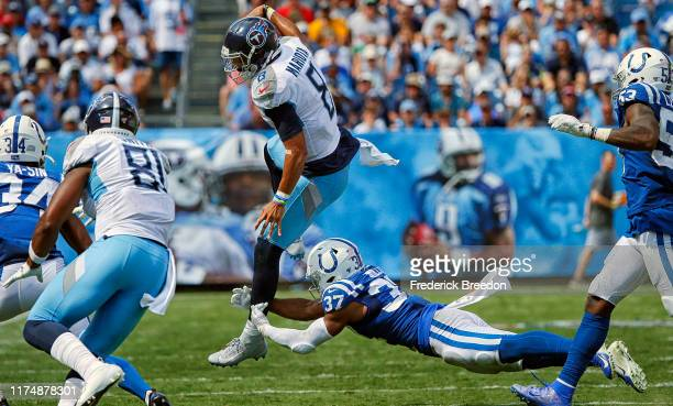Khari Willis of the Indianapolis Colts trips up quarterback Marcus Mariota of the Tennessee Titans during the second half at Nissan Stadium on...
