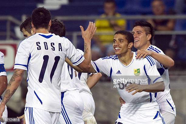 Kharkiv's Brasilian forward Taison is congratulated by his teammates after scoring a goal during the UEFA Europa League playoff second leg football...