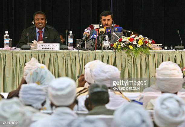 Iranian President Mahmoud Ahmadinejad delivers a speech as he sits next to Sudanese Minister of Religious affairs and Waqf Azhari alTigani alSid...