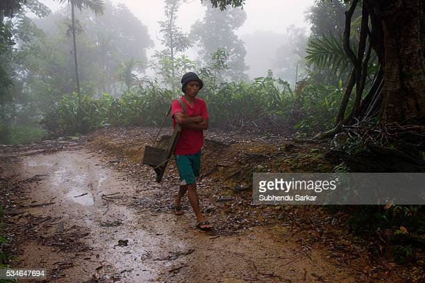 Khasi man walks on a path in the misty atmosphere of Mawlynnong village in Meghalaya Mawlynnong is often called the cleanest village in Asia...