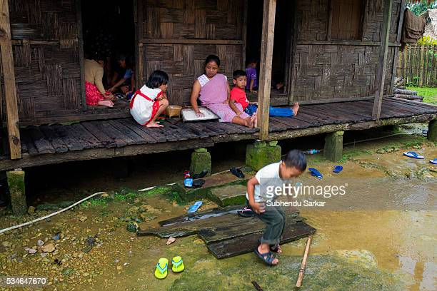 Khasi woman with her children sits at her house at Mawlynnong village in Meghalaya Mawlynnong is often called the cleanest village in Asia Meghalaya...