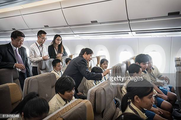 Khaw Boon Wan Singapore's minister of Transport center left tries out the entertainment system with Metta School students aboard an Airbus SE A350...