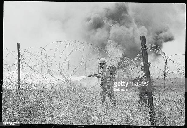 Khe Sanh South Vietnam US Marine uses a flamethrower to burn weeds on perimeter of this embattled Allied outpost here Clearing area in this manner...