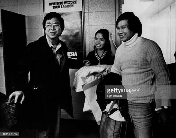 """Khiem Tran, left greets his nephew Do Anh Dung, and nephew's wife, Nguyen Thi Nguyet on their arrival. Family of three were """"boat people."""";"""
