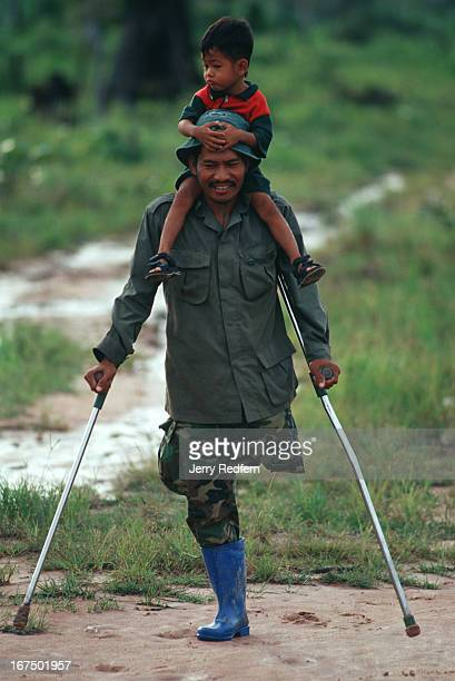 Khin Reth totes his son Khin Sroah to a public meeting in Veal Thom He 'walks' 6 km from his home in the countryside to reach the town The former...