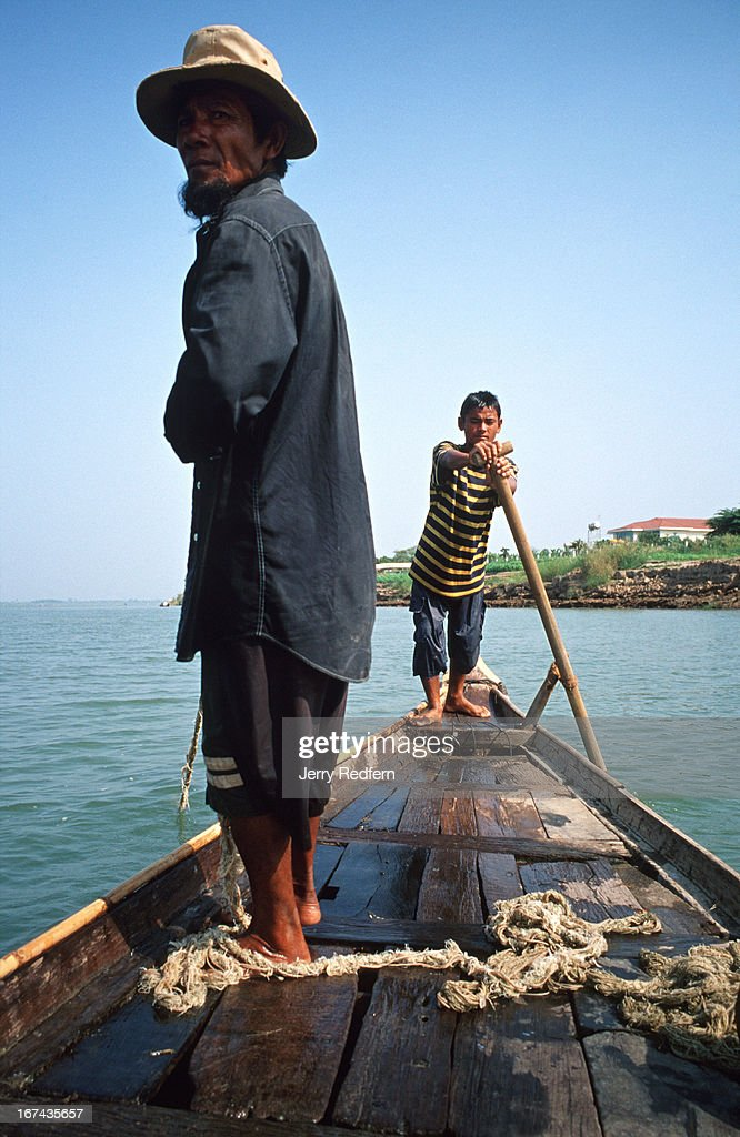 Khin, 55, searches for a spot to set his net in the Mekong River near Phnom Penh as Peh, 19, steers Khin's boat. The net cost $75 new in 1999 and he hopes it will last him several more years. He cannot afford a new one. Khin is a Cham Muslim fisherman who lives on and fishes from his boat on the Mekong. Over the last several years, his catch along the Mekong has dropped dramatically..