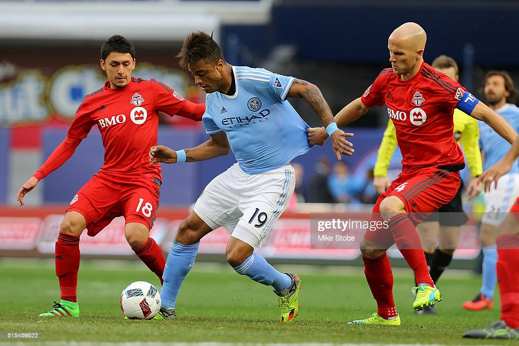 Khiry Shelton #19 of New York City FC carries the ball against Marco Delgado #18 and Michael Bradley #4 of Toronto FC at Yankee Stadium on March 13, 2016 in the Bronx borough of New York City.