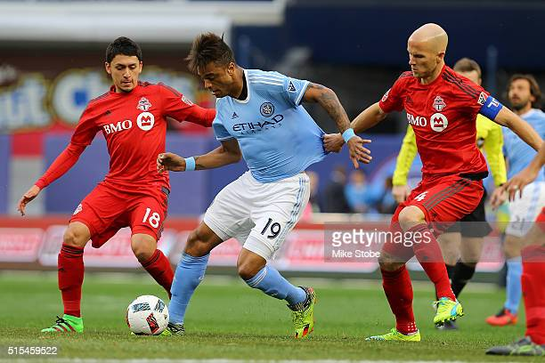 Khiry Shelton of New York City FC carries the ball against Marco Delgado and Michael Bradley of Toronto FC at Yankee Stadium on March 13 2016 in the...