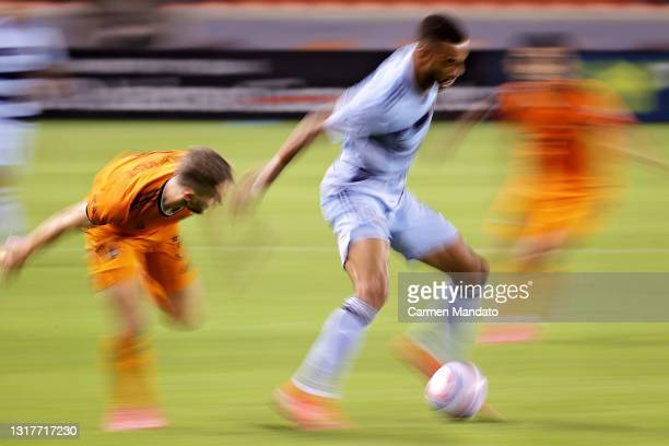 Khiry Shelton of Sporting Kansas City controls the ball ahead of Adam Lundqvist of Houston Dynamo during the first half at BBVA Stadium on May 12,...