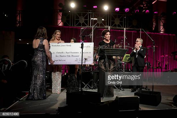 Khloe Kardashian Kourtney Kardashian Kris Jenner and Tommy Hilfiger present a check onstage at the 2016 Angel Ball hosted by Gabrielle's Angel...