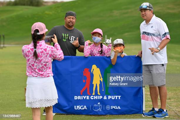 Khloe Kumamoto of the girls 7-9 category poses for a photo with family and friends during the 2021 Drive, Chip and Putt Regional Qualifier at TPC...