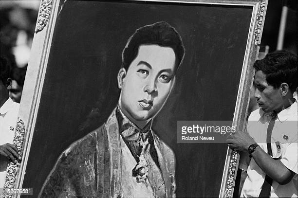 A khmer artist is holding a painting of King Sihanouk at the National Art School near the Royal Palace in Phnom Penh Cambodia Pictures from the book...