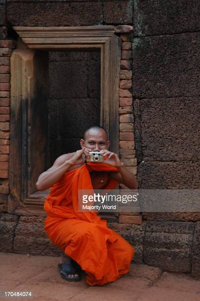 A Khmer monk on his visit to the Banteay Srei Temple takes pictures of the visitors Siem Reap Cambodia December 26 2006