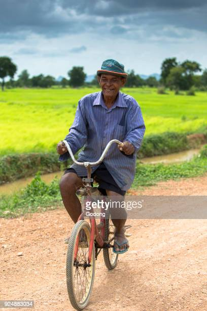 Khmer riding a bicycle on a country road Cambodia