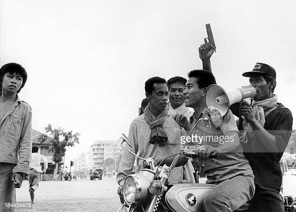 A Khmer Rouge guerrilla soldier holding a gun rides a motorcycle while he and his fellow comrade enter 17 April 1975 Phnom Penh the day Cambodia fell...