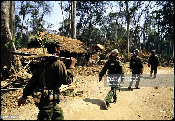 Khmer Rouge guerrillas pass through a deserted village during a patrol in western Cambodia 26th February 1981