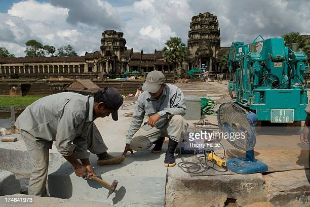 Khmer workers carve stones at the restauration site of the Western causeway leading to Angkor Wat temple The project is managed by the Japanese...