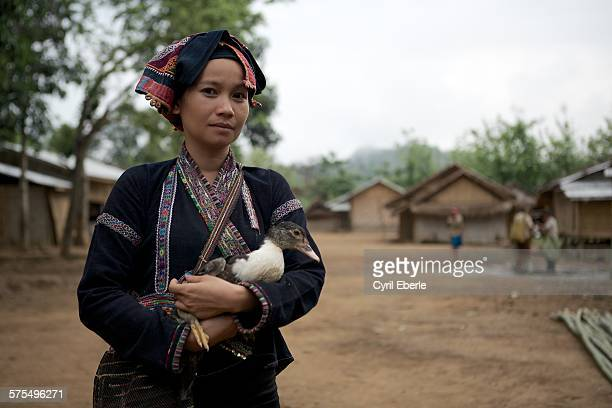Khmu woman in traditional dress holding a duck