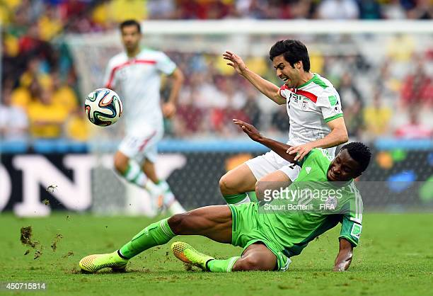 Khosro Heydari of Iran and John Obi Mikel of Nigeria challenge for the ball during the 2014 FIFA World Cup Brazil Group F match between Iran and...