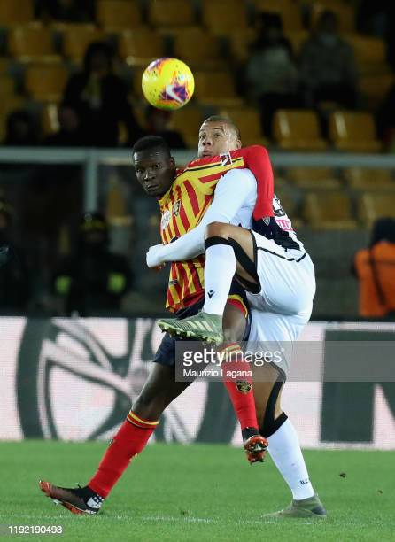 Khouma Babacar of Lecce competes for the ball with Sebastien De Maio of Udinese during the Serie A match between US Lecce and Udinese Calcio at...