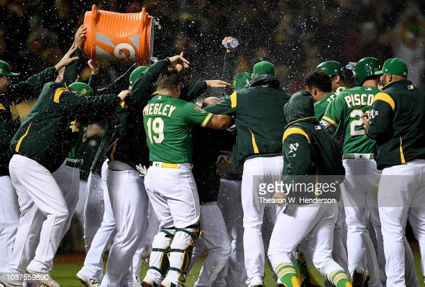 Khris Davis and his teammates of the Oakland Athletics celebrates after Davis hit a walkoff solo home run to defeat the Minnesota Twins 76 in extra...