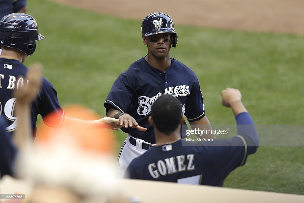 Khris Davis #18 of the Milwaukee Brewers celebrates with Carlos Gomez #27 after gett hit home on a sacrifice fly hit by Mark Reynolds in the bottom of the sixth inning against the San Francisco Giants at Miller Park on August 07, 2014 in Milwaukee, Wisconsin.