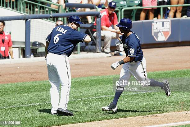 Khris Davis of the Milwaukee Brewers is congratulated by third base coach Ed Sedar after hitting a three run homer in the third inning against the...