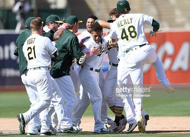 Khris Davis of the Oakland Athletics and his teammates celebrates after Davis hit a walk off rbi double scoring Danny Valencia to defeat the Boston...