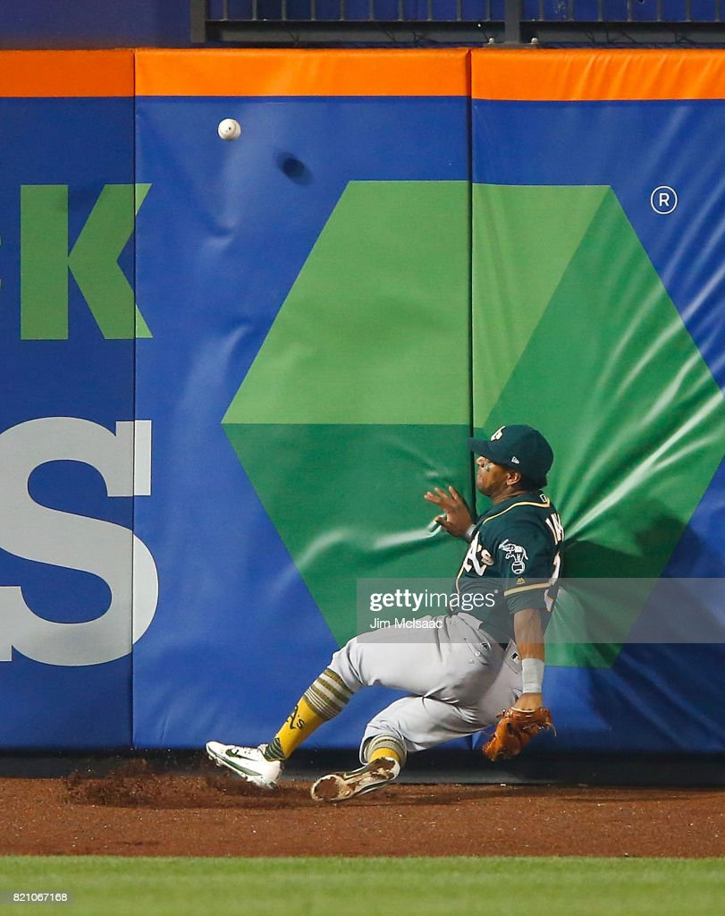 Khris Davis #2 of the Oakland Athletics can't come up with a ball hit in the sixth inning by Jose Reyes #7 of the New York Mets for a triple at Citi Field on July 22, 2017 in the Flushing neighborhood of the Queens borough of New York City.