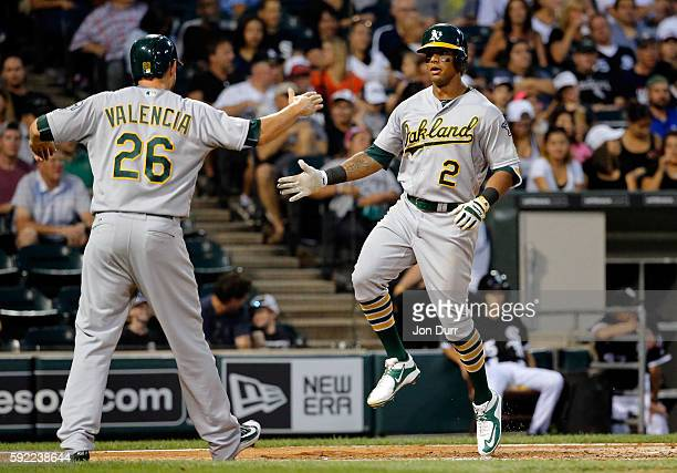 Khris Davis of the Oakland Athletics celebrates with Danny Valencia after hitting a two run home run against the Chicago White Sox during the third...